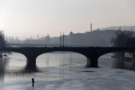 manes: PRAGUE, CZECHOSLOVAKIA - DEC 07, 2015: Manes bridge in central Prague a foggy morning. Silhouette of people walking on the bridge, December 07, 2015 in Prague, Czechoslovakia
