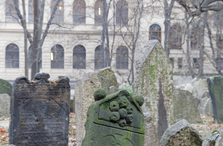 czechia: PRAGUE, CZECHIA - DEC 04, 2015: Old Jewish cemetery with lots of ancient headstones and a church in the background. December 04, 2015 in Prague, Czechia