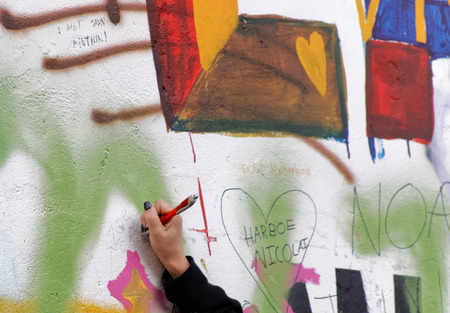 john lennon: PRAGUE, CZECHIA - DEC 05, 2015: Female hand writes on the colorful public John Lennon Wall where there is a continous graffiti painting going on by tourists. December 05, 2015 in Prague, Czechia