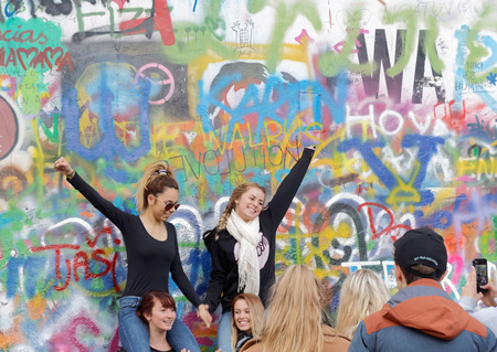 czechia: PRAGUE, CZECHIA - DEC 05, 2015: Two happy woman in front of the colorful public John Lennon Wall where there is a continous graffiti painting going on by tourists. December 05, 2015 in Prague, Czechia