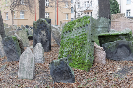headstones: PRAGUE, CZECHIA - DEC 04, 2015: Old Jewish cemetery with lots of ancient headstones in disorder and hoses in the background. December 04, 2015 in Prague, Czechia Editorial