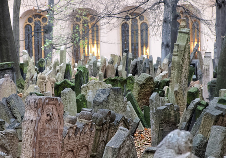 headstones: PRAGUE, CZECHIA - DEC 04, 2015: Old Jewish cemetery with lots of ancient headstones and a church in the background. December 04, 2015 in Prague, Czechia