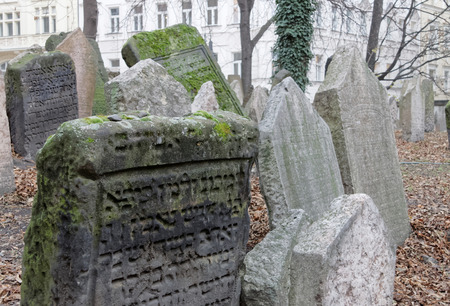 czechia: PRAGUE, CZECHIA - DEC 04, 2015: Old Jewish cemetery, close-up of ancient headstones in disorder. SHort depth of focus. December 04, 2015 in Prague, Czechia