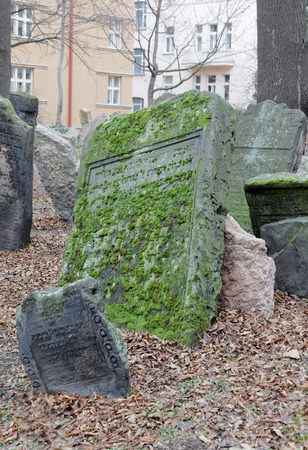 jewish houses: PRAGUE, CZECHIA - DEC 04, 2015: Old Jewish cemetery with lots of ancient headstones in disorder and houses in the background. December 04, 2015 in Prague, Czechia