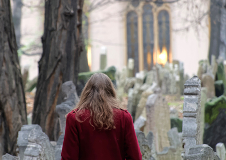 headstones: PRAGUE, CZECHIA - DEC 04, 2015: Old Jewish cemetery with lots of ancient headstones and a woman looking at the graves. December 04, 2015 in Prague, Czechia