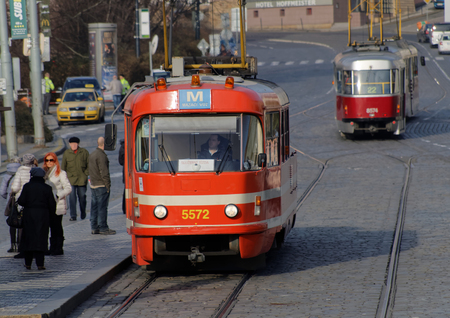 streetcar: PRAGUE, CZECHIA - DEC 04, 2015: Two red and white vintage tram in evening light driving on a cobblestone street in the city. People waiting. December 04, 2015 in Prague, Czechia Editorial