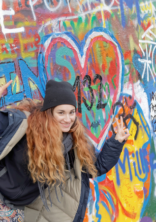 john lennon: PRAGUE, CZECHIA - DEC 05, 2015: Smiling woman with red hair in front of the colorful public John Lennon Wall where there is a continous graffiti painting going on by tourists. December 05, 2015 in Prague, Czechia Editorial