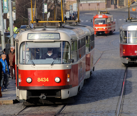 streetcar: PRAGUE, CZECHIA - DEC 04, 2015: Three red and white vintage tram driving on a cobblestone street in the city. Man walking. December 04, 2015 in Prague, Czechia Editorial