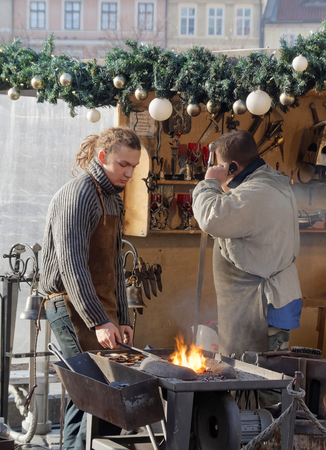 medieval blacksmith: PRAGUE, CZECHIA - DEC 03, 2015: Two blacksmith working in a public square. December 03, 2015 in Prague, Czechia