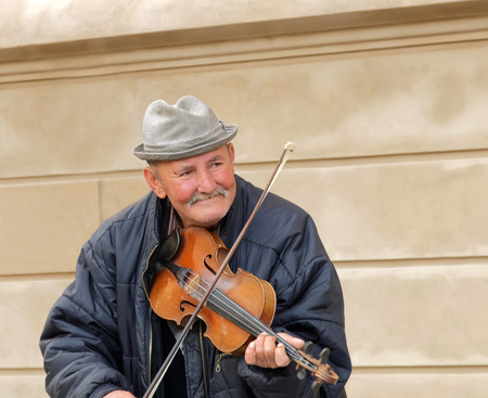solo violinist: PRAGUE, CZECHIA - DEC 04, 2015: Front view of a smiling old man playing the violinin in a public square, tourists in the background. December 04, 2015 in Prague, Czechia