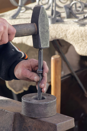 smithery: The hands of a blacksmith working with his hammer Editorial