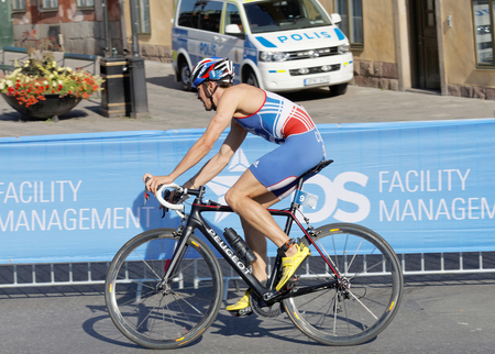 dorian: STOCKHOLM, SWEDEN - AUG 23, 2015: Side view of Dorian Coninix (FRA) cycling in the Mens ITU World Triathlon series event August 23, 2015 in Stockholm, Sweden