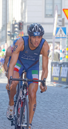 competitor: STOCKHOLM, SWEDEN - AUG 23, 2015: Luca Facchinetti (ITA) cycling followed by a triathlon competitor in the Mens ITU World Triathlon series event August 23, 2015 in Stockholm, Sweden