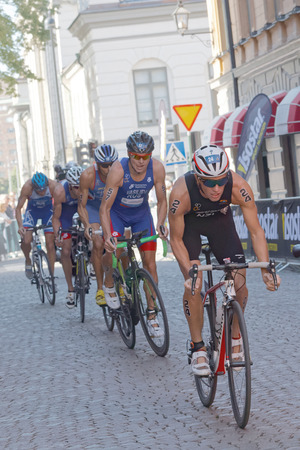 vasiliev: STOCKHOLM, SWEDEN - AUG 23, 2015: Ryan Sissons (NZL) and a group of triathlon competitors cycling in the Mens ITU World Triathlon series event August 23, 2015 in Stockholm, Sweden Editorial