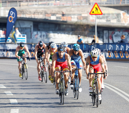 gomez: STOCKHOLM, SWEDEN - AUG 23, 2015: TConcentrated colorful triathletes cycling, Javier Gomez Noya (ESP) in the lead in the Mens ITU World Triathlon series event August 23, 2015 in Stockholm, Sweden