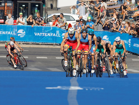 gomez: STOCKHOLM, SWEDEN - AUG 23, 2015: Spanish triathletes Gomez, Hernandez and large group of competitors cycling uphill in the Mens ITU World Triathlon series event August 23, 2015 in Stockholm, Sweden