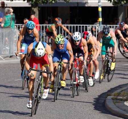 gomez: STOCKHOLM, SWEDEN - AUG 23, 2015:  Javier Gomez Noya followed by cycling triathlon competitors in the Mens ITU World Triathlon series event August 23, 2015 in Stockholm, Sweden