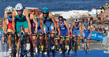 gomez: STOCKHOLM, SWEDEN - AUG 23, 2015: Stuggling, muscular triathlon competitors including Aaron Royle and Javier Gomez cycling uphill in the Mens ITU World Triathlon series event August 23, 2015 in Stockholm, Sweden