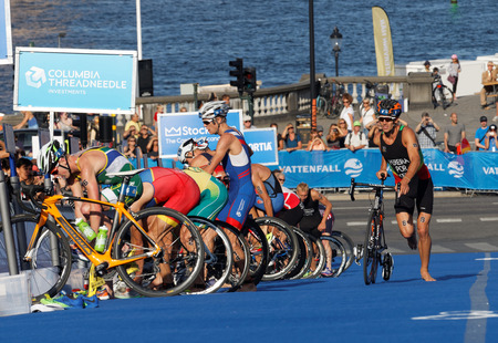 bending down: STOCKHOLM, SWEDEN - AUG 23, 2015: Triathletes bending down and parking cycles in the transition zone in the Mens ITU World Triathlon series event August 23, 2015 in Stockholm, Sweden