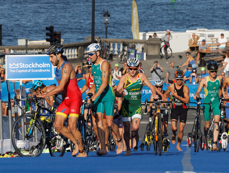 cycles: STOCKHOLM, SWEDEN - AUG 23, 2015: Dramatic sceene of group of triathletes parking the cycles in the transition zone in the Mens ITU World Triathlon series event August 23, 2015 in Stockholm, Sweden