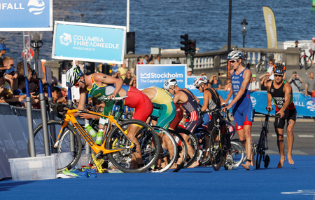 cycles: STOCKHOLM, SWEDEN - AUG 23, 2015: Triathletes bending down and parking cycles in the transition zone in the Mens ITU World Triathlon series event August 23, 2015 in Stockholm, Sweden