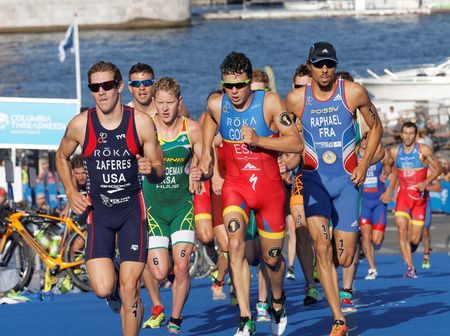 gomez: STOCKHOLM, SWEDEN - AUG 23, 2015: Close-up of group of running triathletes including the leader Javier Gomez wearing sun glasses in the Mens ITU World Triathlon series event August 23, 2015 in Stockholm, Sweden