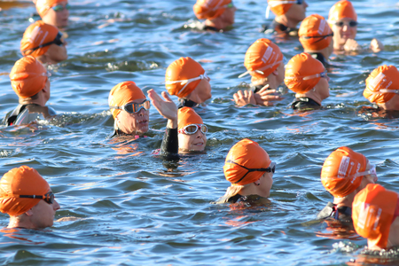 woman squirt: STOCKHOLM - AUG 23, 2015: Waving triathlete  wearing orange bathing caps waiting for the start in the water at ITU World Triathlon event in Stockholm, 2015 Editorial