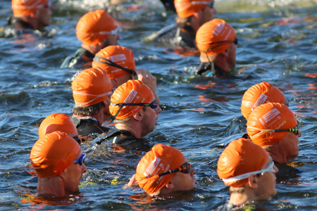 waive: STOCKHOLM - AUG 23, 2015: Close-up of group of male swimmers wearing orange bathing caps at ITU World Triathlon event in Stockholm, 2015