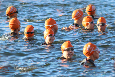waive: STOCKHOLM - AUG 23, 2015: Smiling female triathlete  wearing orange bathing caps and glasses waiting for the start in the water at ITU World Triathlon event in Stockholm, 2015