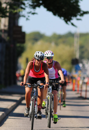 tanktop: STOCKHOLM - AUG 23, 2015: Cycling woman wearing red tank-top followed by de-focused competitors at ITU World Triathlon event in Stockholm, 2015 Editorial