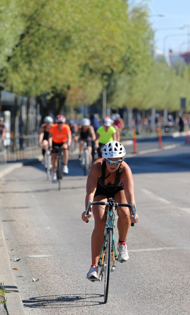 tanktop: STOCKHOLM - AUG 23, 2015: Cycling woman wearing black tank-top and white helmet followed by competitors, trees in background at ITU World Triathlon event in Stockholm, 2015 Editorial