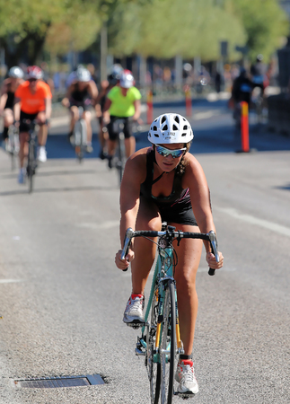 tanktop: STOCKHOLM - AUG 23, 2015: Cycling woman wearing black tank-top and white helmet followed by competitors at ITU World Triathlon event in Stockholm, 2015