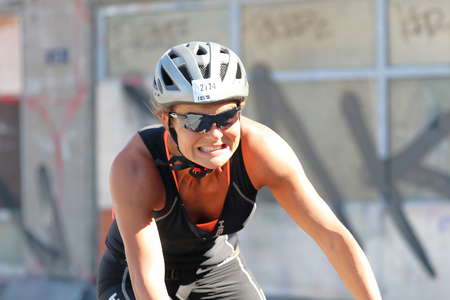 tanktop: STOCKHOLM - AUG 23, 2015: Smiling, cycling woman wearing black tank-top and white sports helmet, close-up at ITU World Triathlon event in Stockholm, 2015