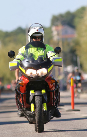 motorcycle officer: STOCKHOLM - AUG 23, 2015: Man in green vest driving motorcycle working as officer at ITU World Triathlon event in Stockholm, 2015 Editorial