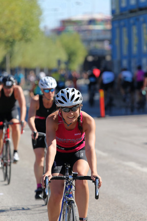 tanktop: STOCKHOLM - AUG 23, 2015: Smiling, cycling woman wearing pink tank-top followed by de-focused competitors at ITU World Triathlon event in Stockholm, 2015 Editorial