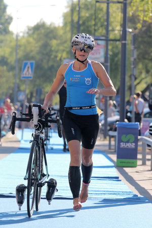 tanktop: STOCKHOLM - AUG 23, 2015: Woman wearing blue tank-top running barefoot with bicycle in the triathlon transition zone at ITU World Triathlon event in Stockholm, 2015