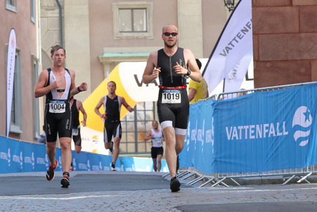 differnt: STOCKHOLM - AUG 23, 2015: Four running men at differnt distance in an cobblestone alley at ITU World Triathlon event in Stockholm, 2015 Editorial