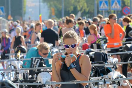swim goggles: STOCKHOLM - AUG 23, 2015: Beautiful woman fixing the swim goggles in the triathlon transition zone before the triathlon race at ITU World Triathlon event in Stockholm, 2015 Editorial