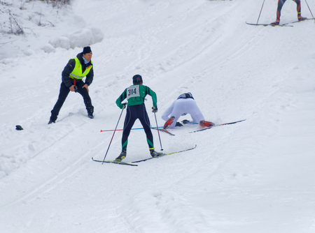 uphill: STOCKHOLM - JAN 24, 2016: Two cross country skiing men sprinting uphill, one is falling at the Stockholm Ski Marathon event January 24, 2016 in Stockholm, Sweden