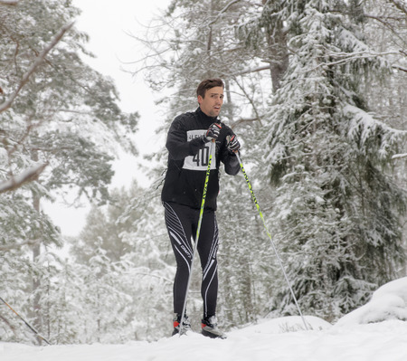 distrustful: STOCKHOLM - JAN 24, 2016: Distrustful cross country skiing man in the beautiful forest at the Stockholm Ski Marathon event January 24, 2016 in Stockholm, Sweden