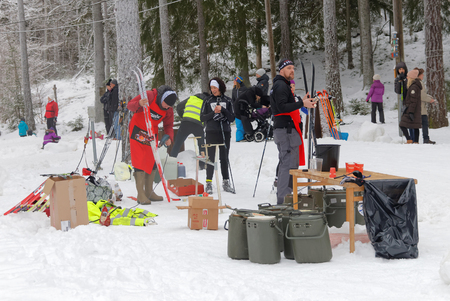 water skiers: STOCKHOLM - JAN 24, 2016: Officials fixing skies and offer water and blueberry soup to the cross country skiers at the Stockholm Ski Marathon event January 24, 2016 in Stockholm, Sweden
