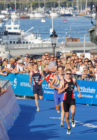 chased: STOCKHOLM - AUG 23, 2015: Running triathlete Schilling chased by Gabriel Sandor and Sharp at the finish at the Mens ITU World Triathlon series event August 23, 2015 in Stockholm, Sweden
