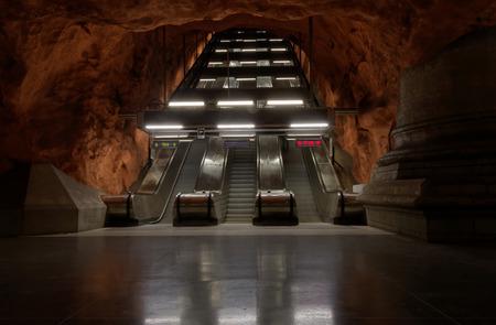 STOCKHOLM - JAN 28, 2016: Escalator in the beautiful orange subway station Radhuset in Stockholm. January 28, 2016 in Stockholm, Sweden Editorial