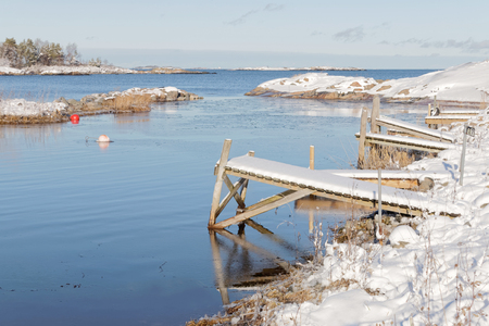 floaters: Small wodden bridges covered with snow in the wintry archipelago