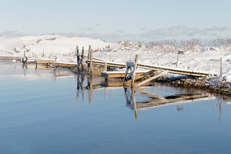 floaters: Small wodden bridges reflecting in the water in the wintry archipelago Stock Photo