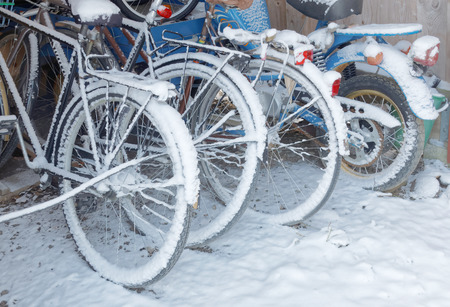 moped: Snowy wheels of bicycles and a moped