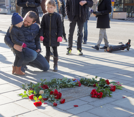 unsolved: STOCKHOLM, SWEDEN - FEB 28, 2016: Father and children showing respect to the murdered prime minister Olof Palme where he got shot at Sveavagen on the memorial day 30 years after the murder. February 28, 2016, Stockholm, Sweden