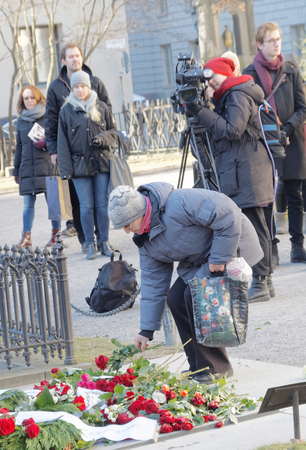 unsolved: STOCKHOLM, SWEDEN - FEB 28, 2016: Memorial day 30 years after the murder of the swedish prime mininster Olof Palme. Old lady putting roses on his grave. February 28, 2016, Stockholm, Sweden Editorial