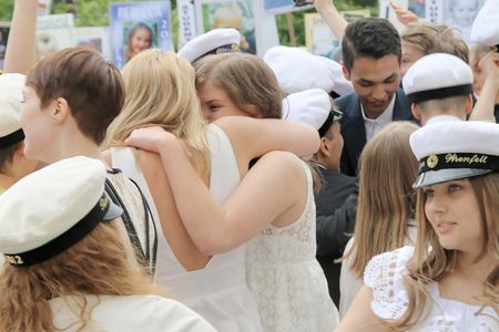 finishing school: STOCKHOLM, SWEDEN - JUN 10, 2015: Group of happy teenages wearing graduation caps hugging and celebrating the graduation after finishing high school at the school Globala gymnasiet, June 10, 2015, Stockholm, Sweden Editorial