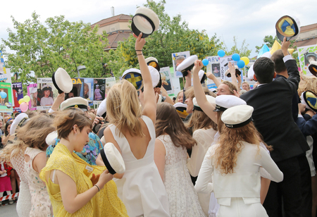 finishing school: STOCKHOLM, SWEDEN - JUN 10, 2015: Group of happy teenagers dancing and raising the graduation caps celebrating the graduation after finishing high school at the school Globala gymnasiet, June 10, 2015, Stockholm, Sweden